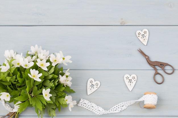 Ramo de flores de primavera sobre un fondo de madera azul, tijeras y tres corazones