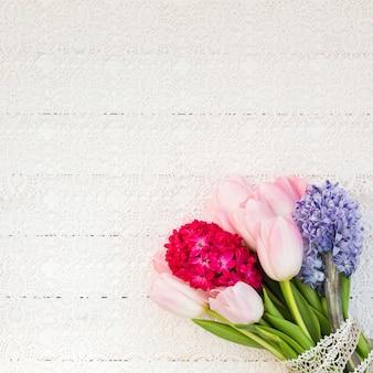 Ramo de flores de primavera sobre mantel blanco. vista superior, espacio de copia