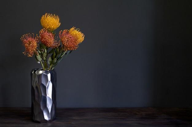 Ramo de flores de protea exóticas amarillas y anaranjadas en un jarrón de metal sobre un fondo oscuro