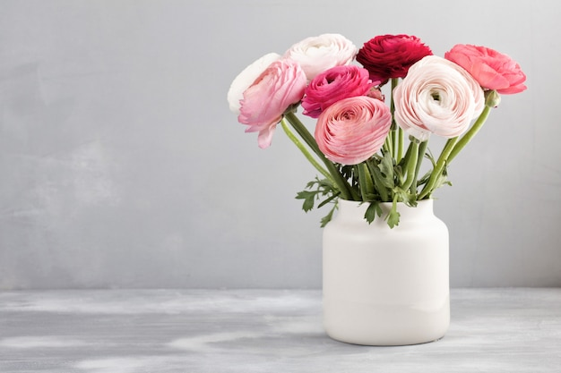 Ramo de flores de ranúnculo rosa y blanco sobre la pared gris