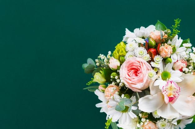 Ramo de flores con regalo en verde flat lay