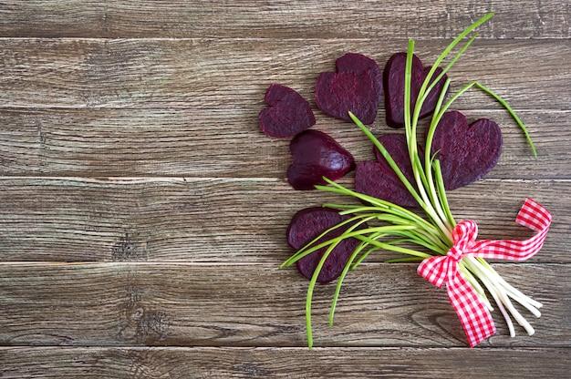 Un ramo de flores de rodajas de remolacha hervida y cebolla verde sobre un fondo de madera. amar la remolacha. concepto de alimentación saludable feliz día de san valentín. copia espacio