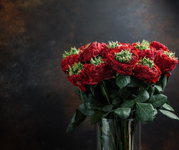 Ramo de flores rojas en florero de vidrio en fondo oscuro