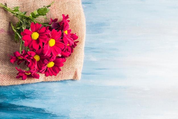 Ramo de flores rojas sobre lienzo sobre mesa.