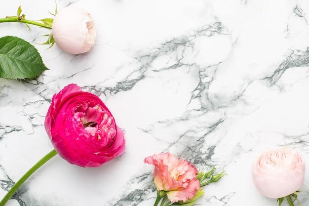 Ramo de flores rosadas y blancas sobre fondo de mármol con copyspace