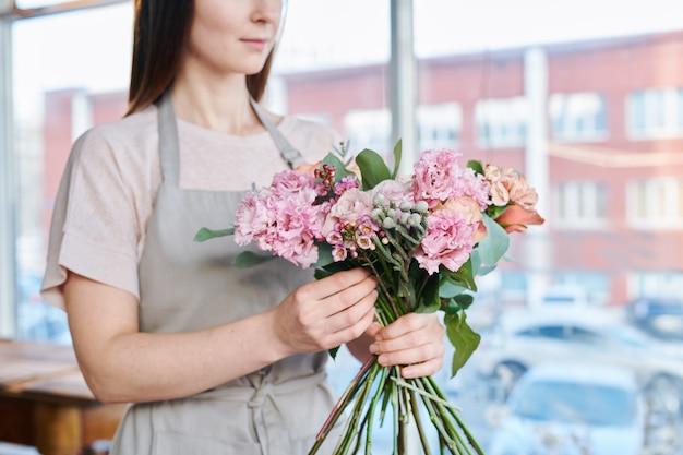 Ramo de flores rosadas frescas sostenidas por una joven florista contemporánea trabajando sobre un nuevo ramo