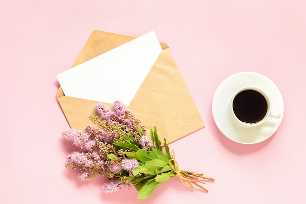 Ramo de flores rosadas, sobre con tarjeta blanca en blanco para texto y taza de café