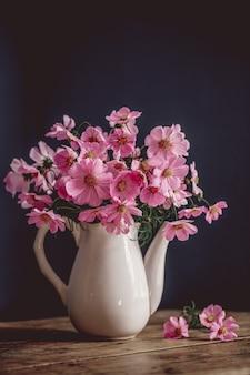 Ramo de flores rosas. cosmea fondo azul, platos blancos