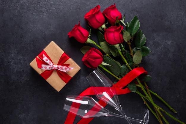 Ramo de flores rosas rojas, caja de regalo, copas de champán sobre fondo de piedra negro tarjeta de felicitación del día de san valentín