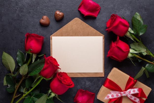 Ramo de flores rosas rojas, sobre, caja de regalo sobre fondo de piedra negro tarjeta de felicitación del día de san valentín