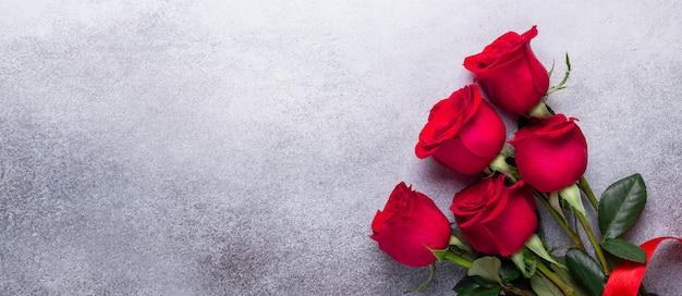 Ramo de flores rosas rojas sobre fondo de piedra día de san valentín