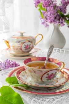 Ramo de flores rosas (rosas) y servicio blanco en un alféizar.