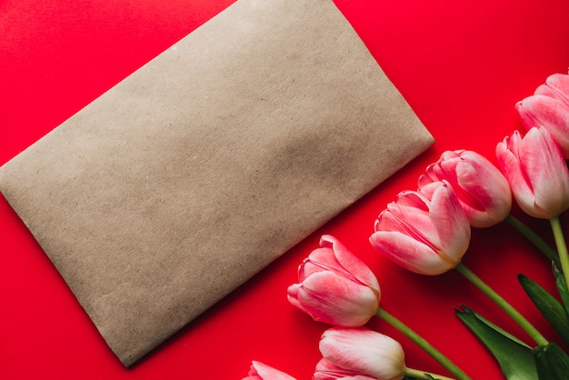 Ramo de flores rosas de tulipanes sobre un fondo rojo.
