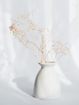 Ramo de flores secas de gypsophila en un jarrón blanco sobre pared ligera
