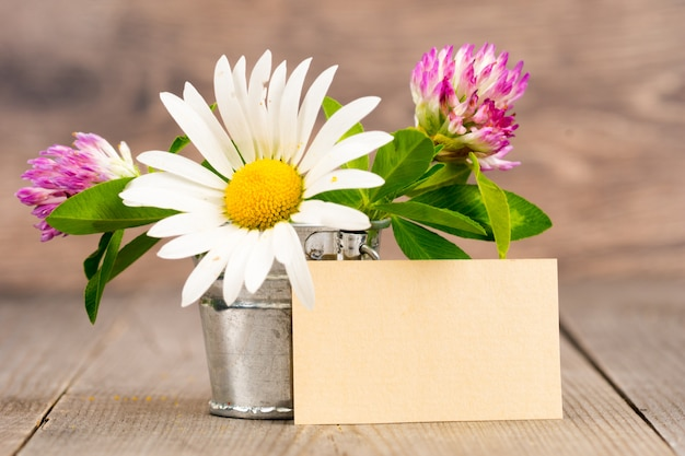 Ramo de flores silvestres en balde de hojalata sobre mesa de madera vieja grunge