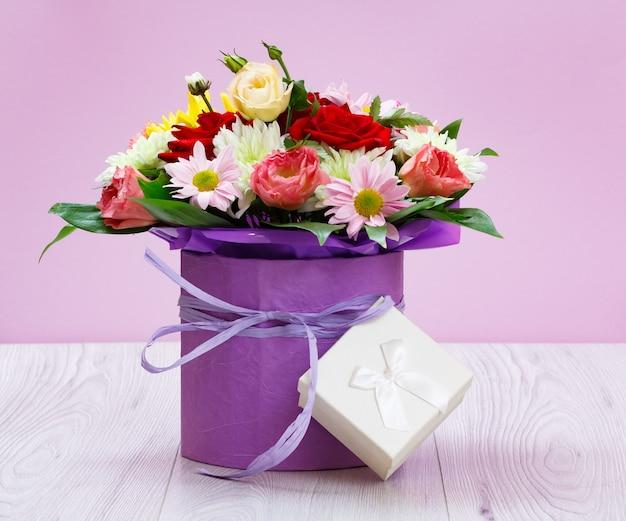 Ramo de flores silvestres y una caja de regalo en las tablas de madera.