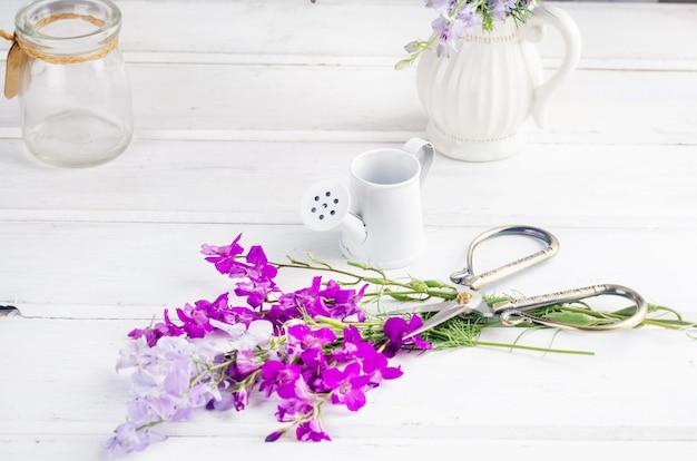 Ramo de flores silvestres de color púrpura en un jarrón de vidrio sobre una mesa blanca en el interior con un lugar para el texto. en blanco para postales. concepto de primavera