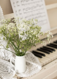 Ramo de flores silvestres en piano blanco con notas. foto retro