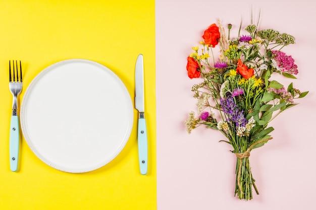 Ramo de flores silvestres y plato, plano, vista superior