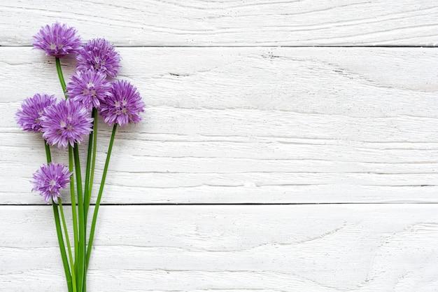 Ramo de flores silvestres púrpuras sobre fondo blanco de madera