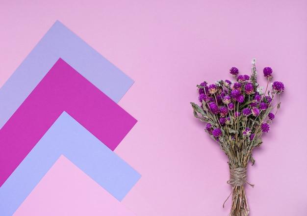 Ramo de flores silvestres secas sobre una superficie rosa, morada y lila