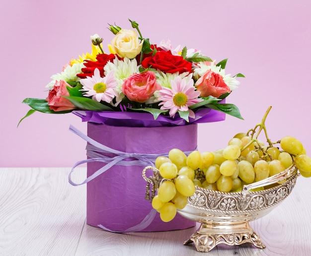 Ramo de flores silvestres y uvas en un jarrón de metal sobre las tablas de madera