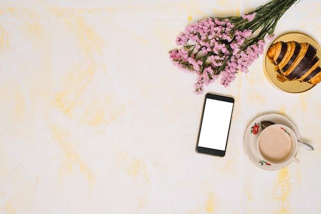 Ramo de flores con smartphone, café y croissant en mesa.