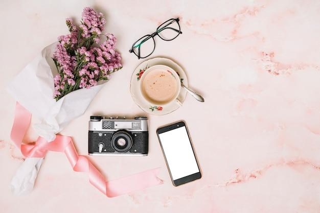 Ramo de flores con smartphone y taza de café.