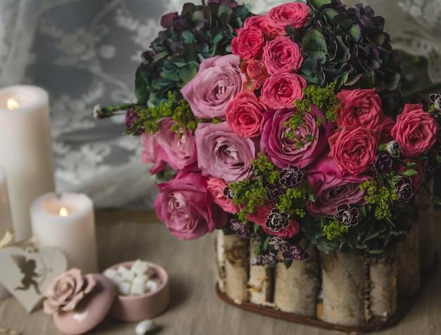 Ramo de flores en un soporte de madera con caramelos y velas.