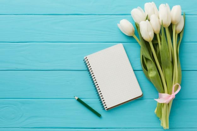 Ramo de flores de tulipán con bloc de notas vacío
