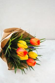 Ramo de flores de tulipán en paquete de papel en mesa blanca