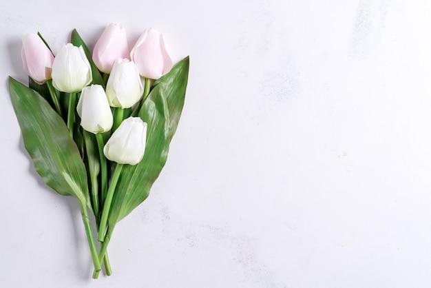 Ramo de flores de tulipán pastel de primavera sobre fondo de piedra, plano con espacio de copia