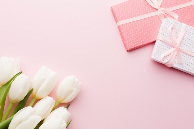 Ramo de flores de tulipán y regalos sobre fondo rosa