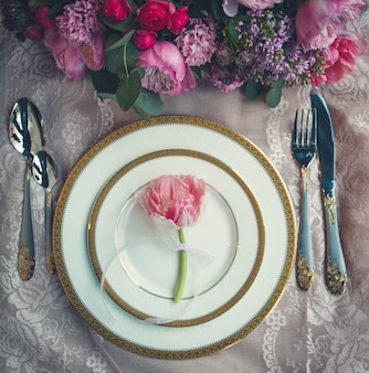 Ramo de flores y tulipán rosa dentro de platos blancos.
