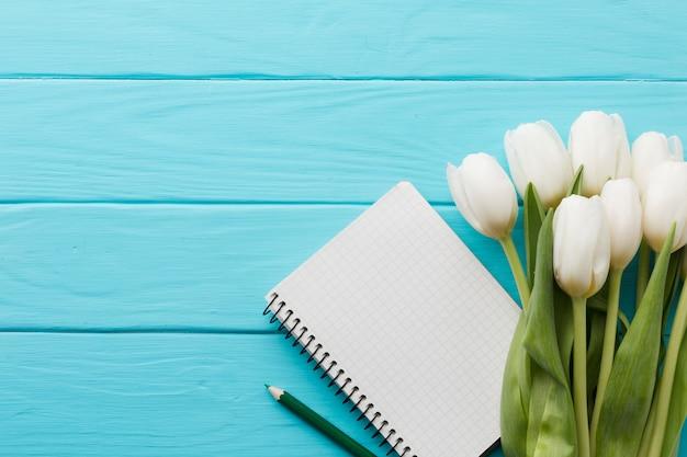 Ramo de flores de tulipán y vista superior del bloc de notas