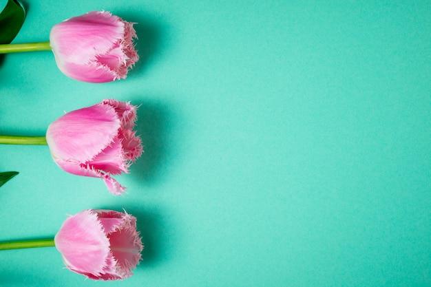 Ramo de flores de tulipanes sobre fondo festivo de color. flores de primavera en tarjeta floral. fondo floral
