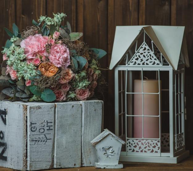 Ramo de flores, vela en la jaula y caja de madera rústica