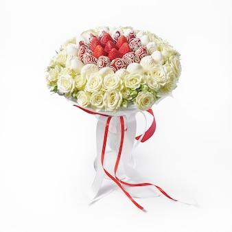 Ramo fresco de rosas blancas y fresas decoradas con chocolate blanco en un jarrón