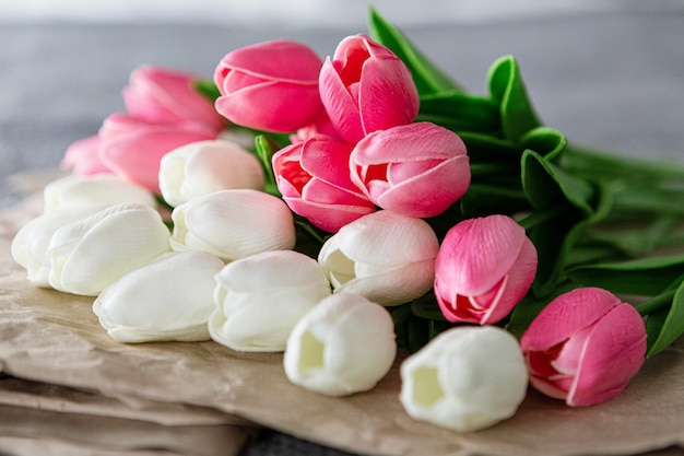 Ramo fresco de tulipanes blancos y rosados sobre papel reciclado sobre fondo gris