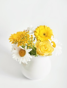 Ramo de hermosas margaritas en florero blanco