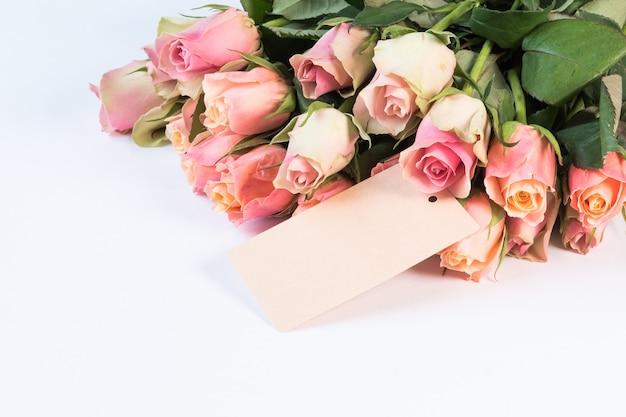 Ramo de hermosas rosas rosadas con una tarjeta aislada sobre fondo blanco