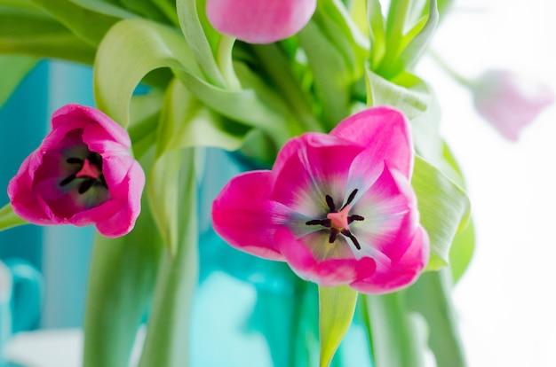 Ramo de hermosas rosas y tulipanes en jarrón tiffany.