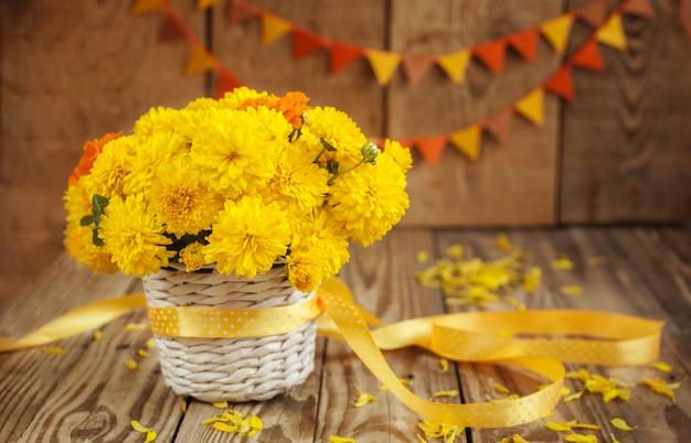 El ramo hermoso de crisantemos amarillos florece en cesta de mimbre en el fondo de madera