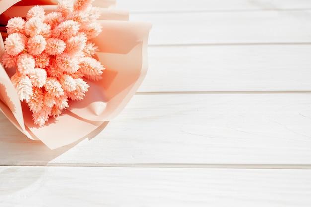 Ramo hermoso de flores rosadas secas en un fondo blanco de madera.