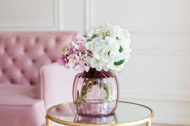 Ramo de hortensias de colores en florero de vidrio vintage en mesa de café en la sala blanca.