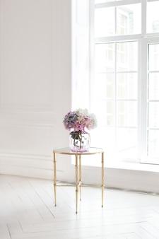 Ramo de hortensias en un florero de cristal en un lujoso interior junto a la ventana. un ramo de flores sobre una mesa en una habitación blanca en casa. el interior clásico de la sala de estar. decoración del hogar. escandinavia.