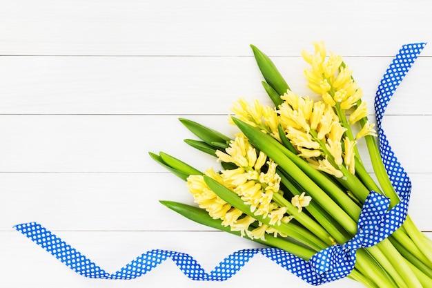 Ramo de jacintos amarillos decorados con cinta azul sobre fondo blanco de madera