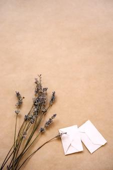 Un ramo de lavanda y dos pequeños sobres hechos a mano sobre papel artesanal para embalaje.