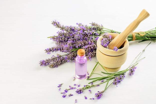 Ramo de lavanda y flores de lavanda en el mortero de madera con maja y aceite de lavanda de piel. estilo de vida aromático y saludable.