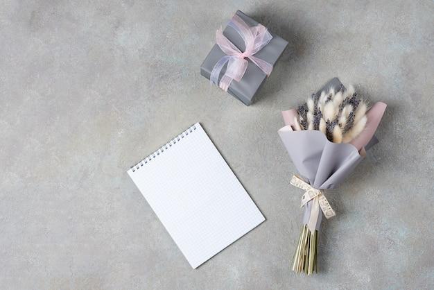 Ramo de lavanda y lagurus con embalaje gris-púrpura con una caja de regalo en un solo color.